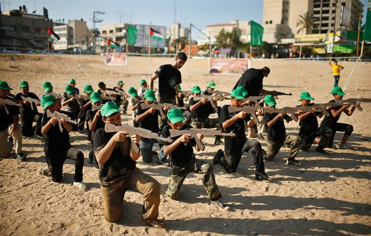 Mahmoud Haniyeh, front left, aims a wooden gun during a military-style exercise at a summer camp organized by the Hamas movement in Gaza City on June 17.