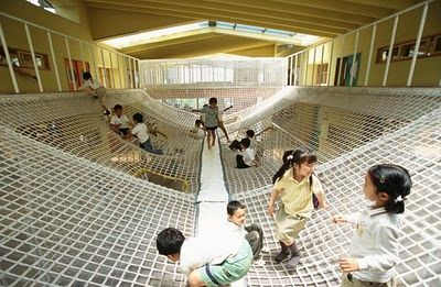 """This big net play feature is provided in the centre of the building and connects the second and third floors. Children enjoy sliding, climbing, jumping and lying down on the net with slope and that helps children's development such as physicality and sociability. The net has become the school's symbol."""