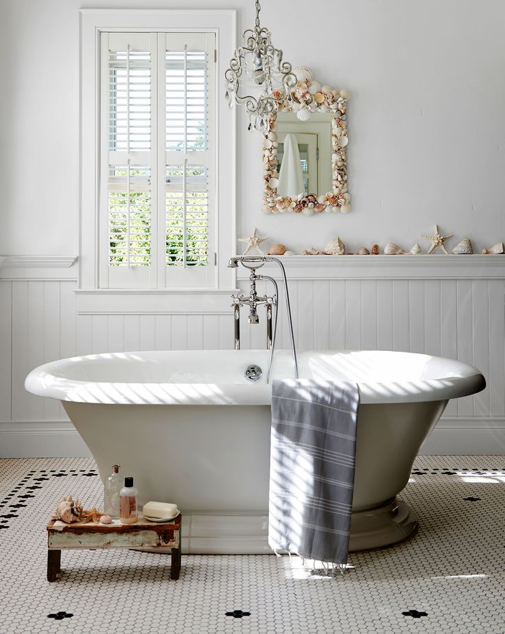 Throughout the house, traditional millwork, such as crown moldings and beadboard, joins modern, clean lines and a zillion windows clad in minimalist shutters. Four windows bathe the master bath's Kohler tub in natural light, while seashells line the chair rail.   - CountryLiving.com