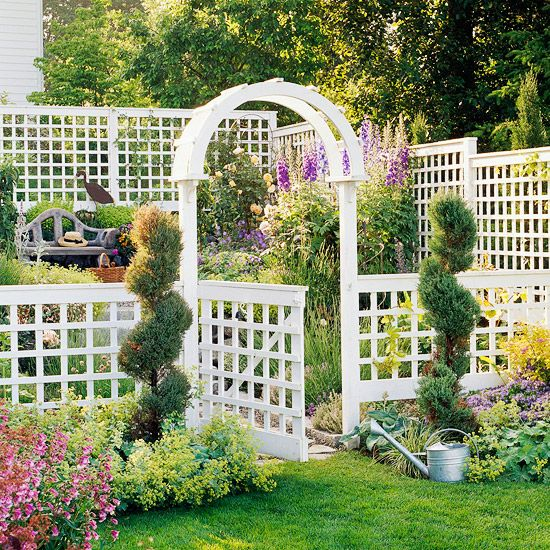 Equal parts arbor and trellis, geometrically spaced latticework gives a pretty structure some formal style.  Many arbors function as a support structure for a gate; this one uses an entrance to designate the border of a garden.  Plant materials can mark an area around an arbor, as with these gently curving topiaries.  Many times a path leads up to, under, and past an arbor, but in this structure, the path begins only after passing into the garden.