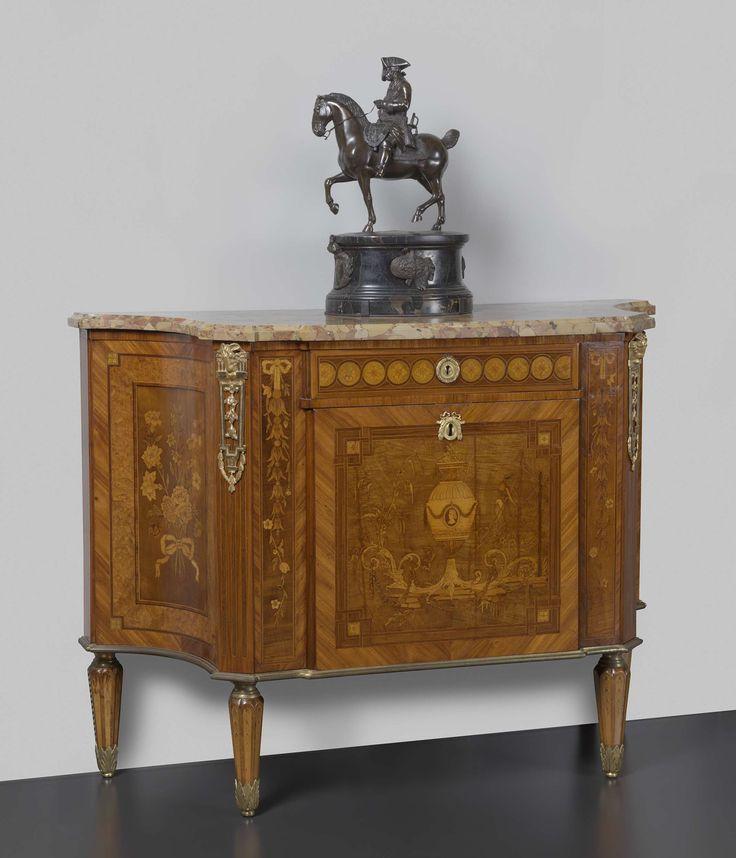 anoniem | Commode, attributed to Matthijs Horrix, c. 1775 - c. 1780 | Eikenhouten commode belijmd met meerdere houtsoorten. De kwartrond gewelfde zijden tonen een boeket met strik. De voorzijde bevat een lade met cirkels met rozetten. De deur eronder toont een vaas met portretmedaillon, acanthusvoluten met festoen, bloemtakken en vogels; langs de voorzijde kloksnoeren aan een strik. De hoekige poten lopen naar onderen taps toe; de voorste hoekstijlen met schijncannelures zijn overhoeks…