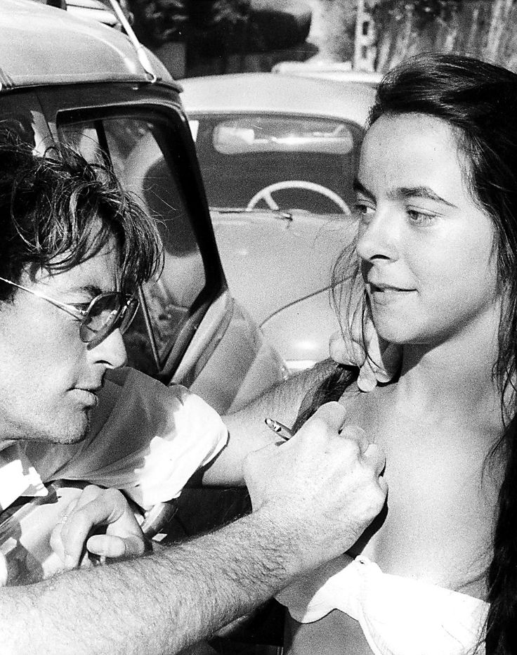 Gregory Peck leans out of his car and autographs the chest of a young fan, ca. 1960's. °