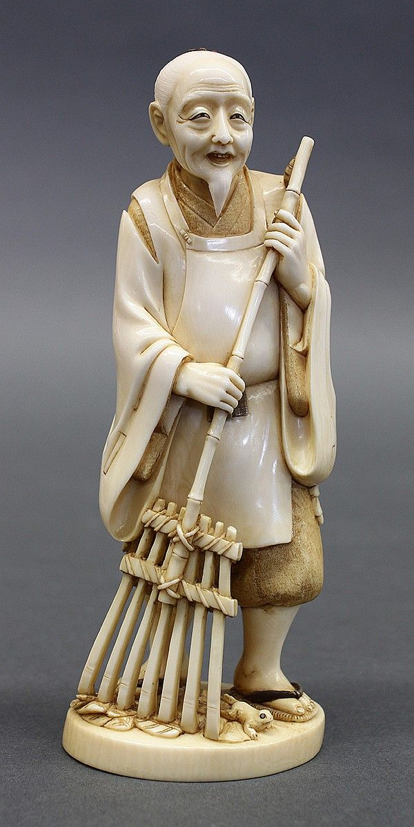 "Japanese ivory okimono, Meiji period, featuring a man sweeping the ground with a rake, a frog by his feet, signature underneath the base, 6""h"