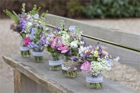 Mix of country garden spring flowers in jam jars