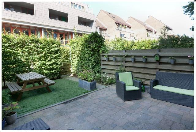 Fraai aangelegde zonnige tuin met terras, elektrisch bedienbaar zonnescherm en achterom. De tuin is gelegen op het westen (middag- en avondzon).