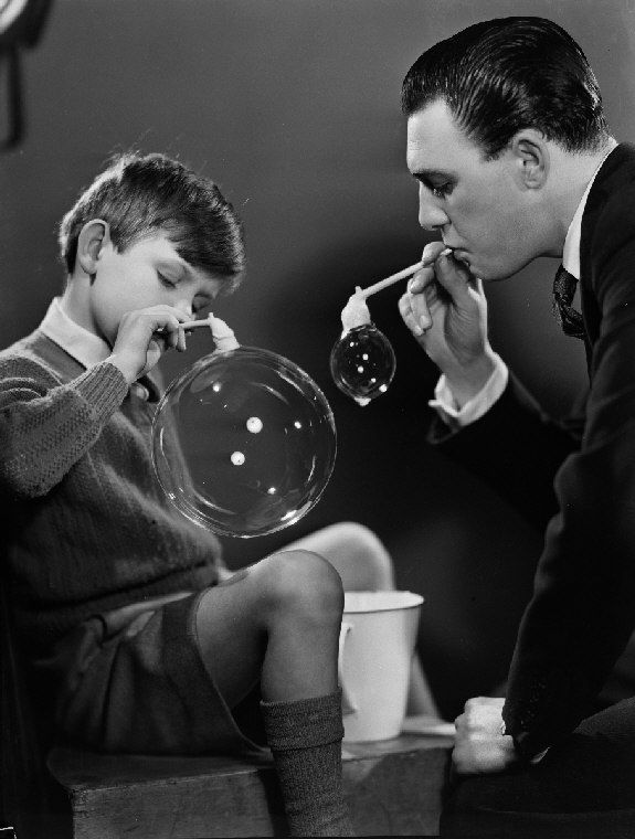 A photograph showing a young boy and a man blowing bubbles, taken by Photographic Advertising Limited, c. 1950.