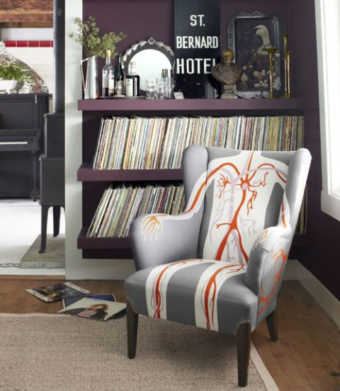 A wingback chair by AK-LH serves as both extra seating and a conversation starter in the dining room, where Case displays her collection of more than 500 albums. The walls wear Farrow & Ball's Brinjal.