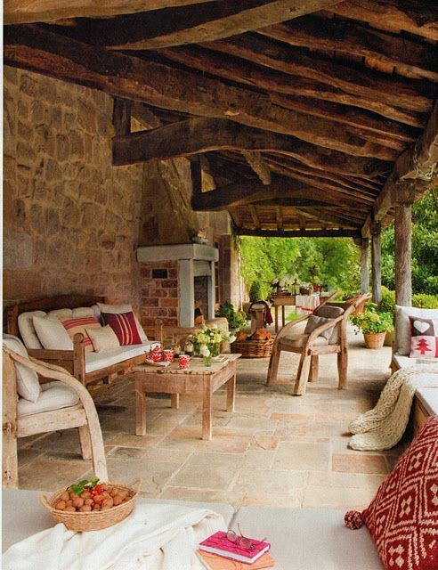 Rustic, homey outdoor living space. Love the blankets, cushions, and fireplace.