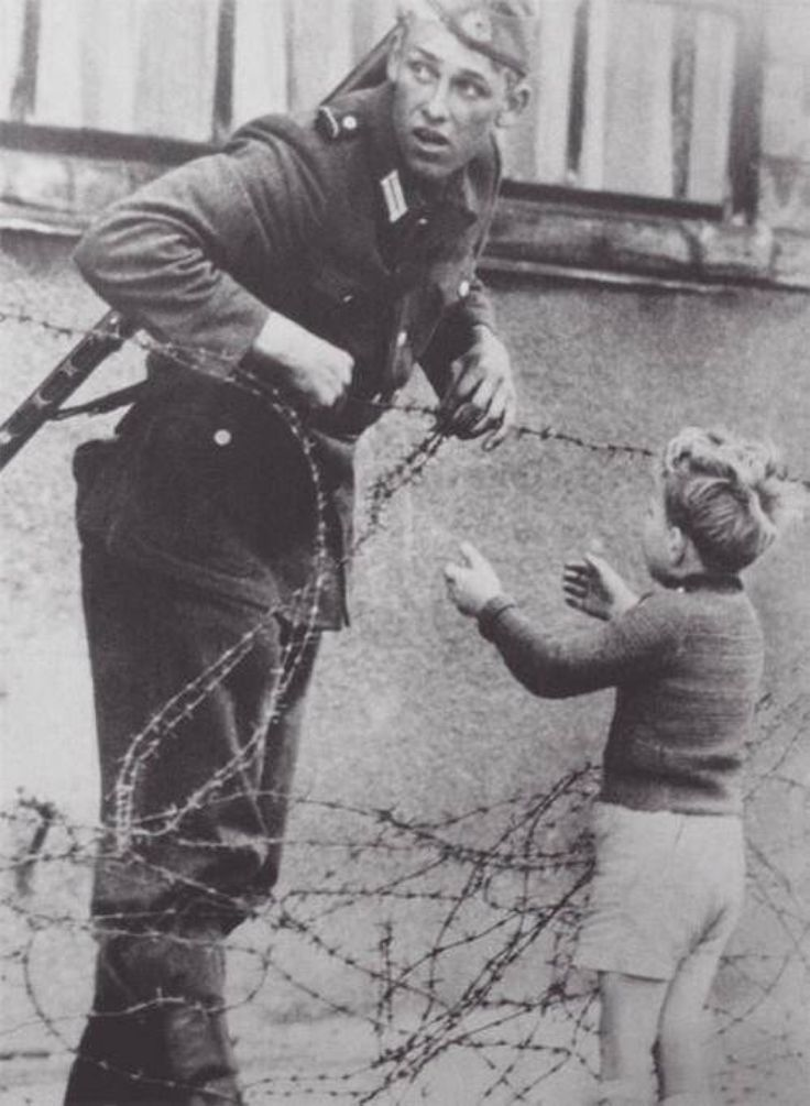 East German soldier helping a boy cross the new Berlin Wall to reunite with his family. 1961.