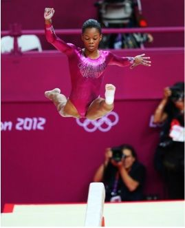 406b: The image shows Gabby Douglass jumping during her beam routine.  The image captures her at the peak of her performance, and she is glorified and looks almost like a superhero as it captures her mid air.  She looks deep in concentration and dedicated.: Floor Exercises, London 2012, Balance Beam, 2012 Olympics, Gabby Douglas, Summer Olympic, Douglas S Performance, First Place
