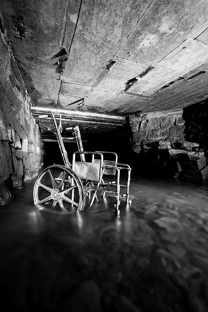 Creepy abandoned wheele chair in underground river shaft