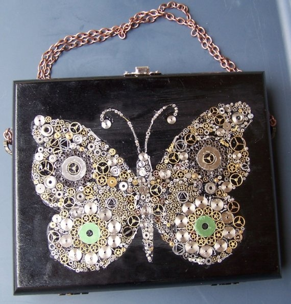 Gear Butterflies. Beautiful black lacquered cigar box with hand-placed gears to create the intricate butterfly design that adorns the front of this box. Copper-toned metal chain handle and a pretty silver-toned metal clasp. Lined with a decorative piece of felt.