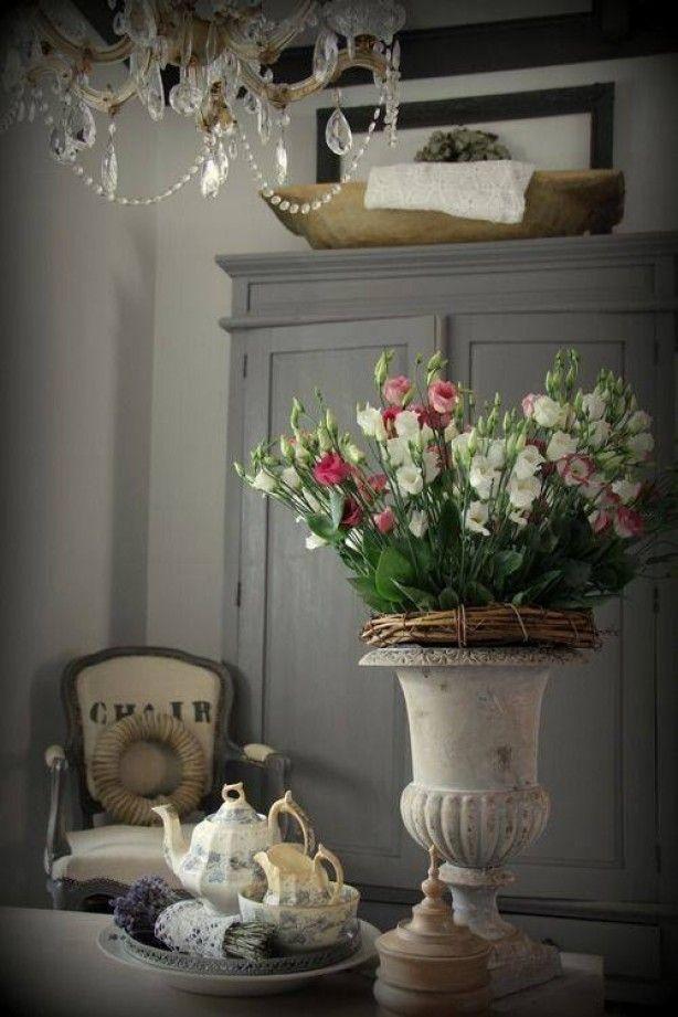 .... Bloemen in het middelpunt van deze foto .Mooi! Een mooie vaas een krans en een mooie bos bloemen....