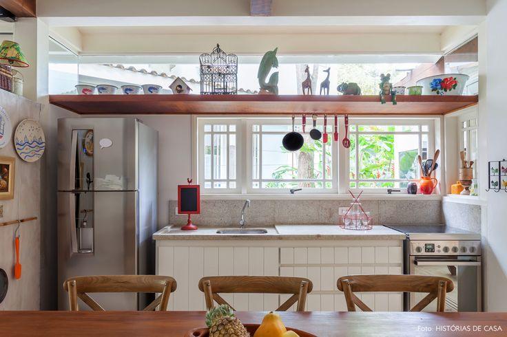 Cozinha tem prateleira suspensa, bancada de granito e mesa de madeira.