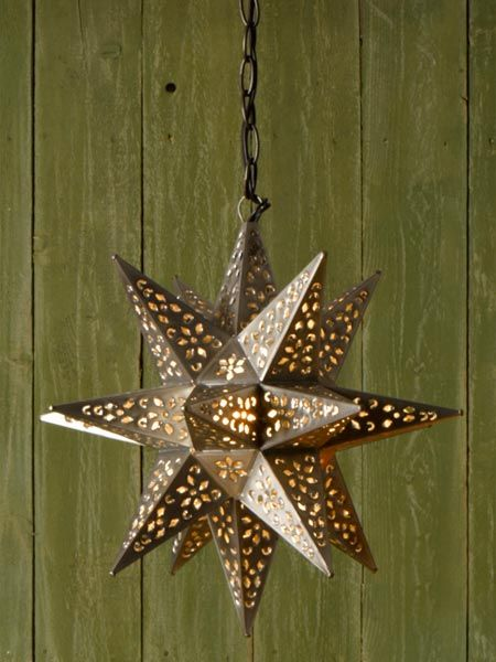 a punched tin with an finish moravian star pendant light hung against a green woodslat wall - Star Pendant Light
