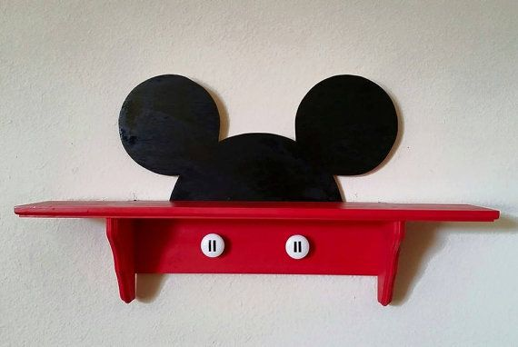 Decorate your childs room with this handmade wooden Mickey Mouse shelf. Measures 17 inches in height, 32 inches wide, and 6.5 inches deep.
