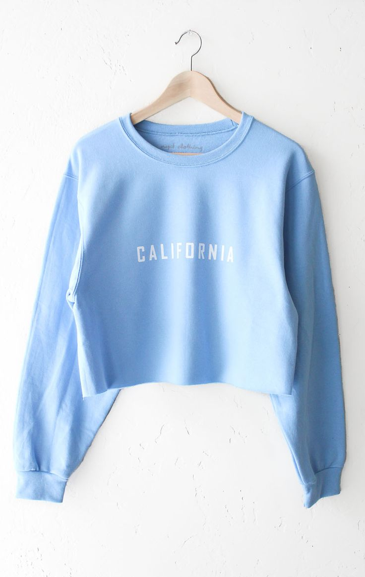 "- Description Details: 'California' cropped sweater in light blue. Brand: NYCT Clothing. Unisex, oversized/loose fit. Measurements: (Size Guide) XS/S: 40"" bust, 18"" length, 35"" sleeve length M/L: 44"""