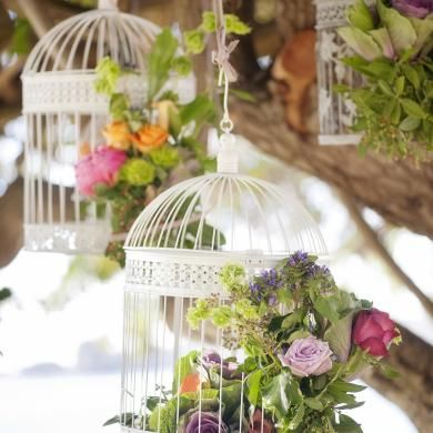 Vintage bird cages filled with whimsical flowers hang from a tree at this pretty garden ceremony. Flowers & Styling by Touched by Angels