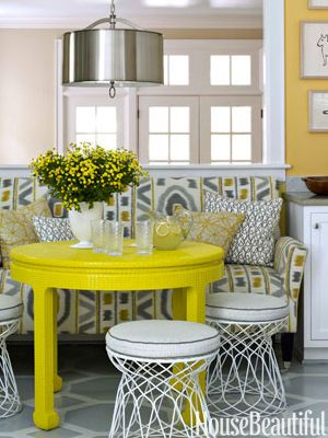 "BRIGHT EAT-IN KITCHEN:  ""yellow walls—Benjamin Moore's Inner Glow—and an even brighter citron table from HB Home brought the white-and-gray Charlotte, North Carolina, kitchen to life. Designer Lindsey Coral Harper turned wire side tables from ABC Carpet & Home into stools. Dark brown floors were transformed with a large geometric pattern, painted by Jay C. Lohmann. Pendant light from Robert Abbey. Hugo Guinness prints from John Derian."""