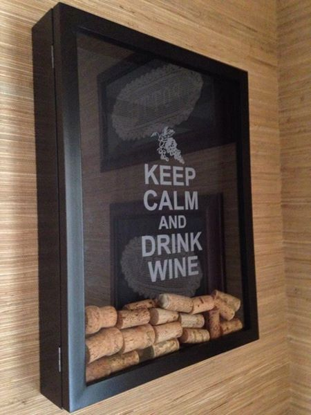 Keep Calm & Drink Wine I went to Hobby Lobby & bought a 12X16 shadow box. Took it to a local Trophy shop & had them etch the words in the glass for me. You drop your cork through a hole on top that you can drill. Keeps it from being took down to drop corks in.