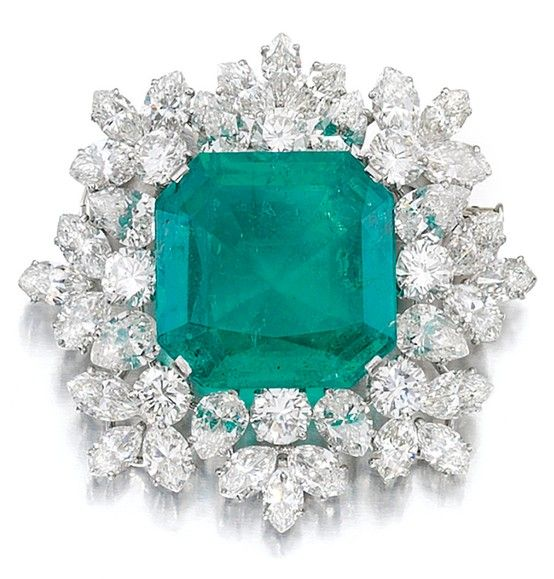 IMPRESSIVE EMERALD AND DIAMOND BROOCH, BULGARI, 1964. Set to the centre with a step-cut emerald weighing 27.57 carats, framed with pear-, marquise-shaped and brilliant-cut diamonds, signed Bulgari, pouch stamped Bulgari.
