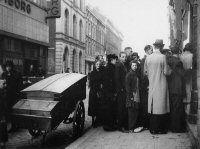 Schaarste aan voedselvoorziening gedurende de bezettingstijd. Tijdens de hongerwinter staan mensen in de rij voor een bakker op de Oude Binnenweg. Links kledingwarenhuis Kreymborg. Datering:1942