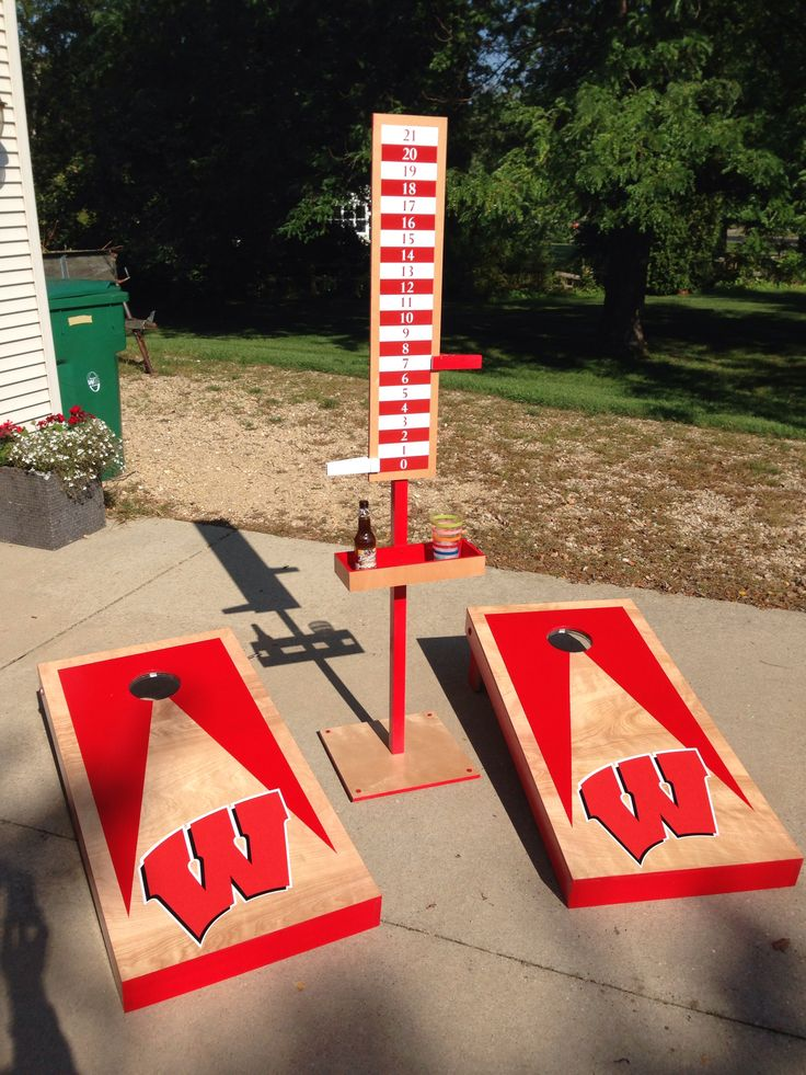 Cornhole: Wisconsin Badgers-themed cornhole set. Includes scoring tower with integrated drink holder and bottle opener. Not shown is a second free-standing drink holder. Holes are illuminated with LED light rings sold online specifically for cornhole boards. Maple construction.