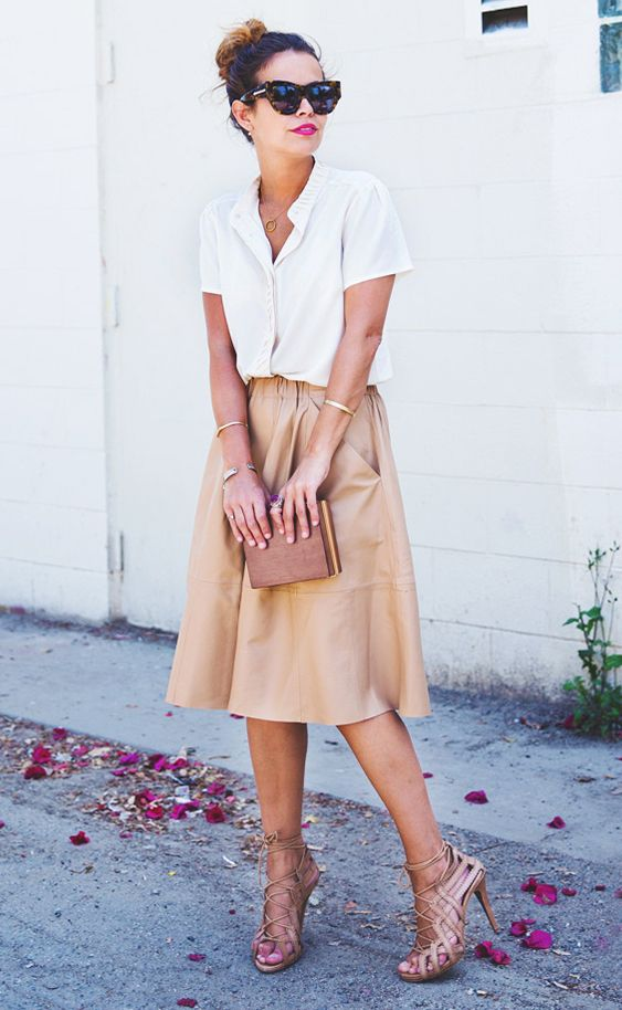 Sara of Collage Vintage wearing a button-up blouse tucked into a leather midi skirt with tan lace up heels