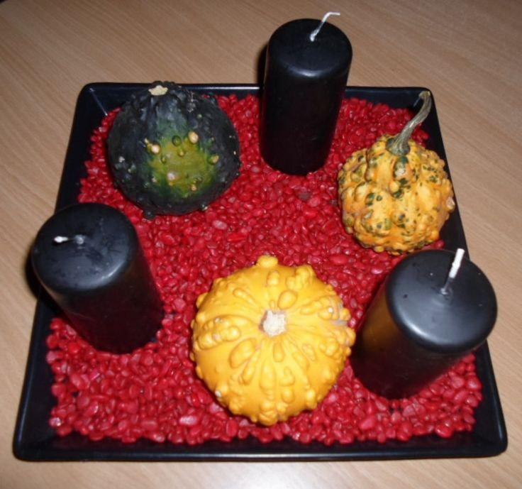 Halloween decoration with red stones, black candles and little pumpkins.