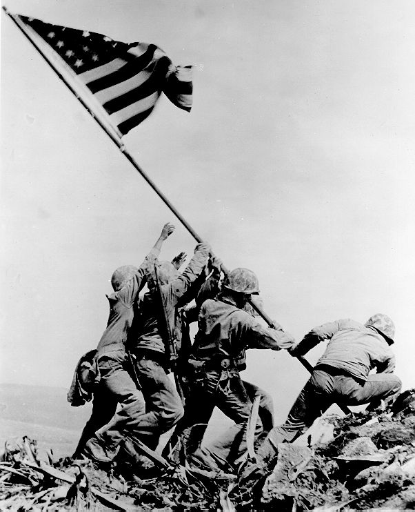 World War II - iconic image of the raising of the American flag at Iwo Jima.  Taken on February 23, 1945, by Joe Rosenthal. It depicts five United States Marines and a U.S. Navy corpsman raising the flag atop Mount Suribachi.