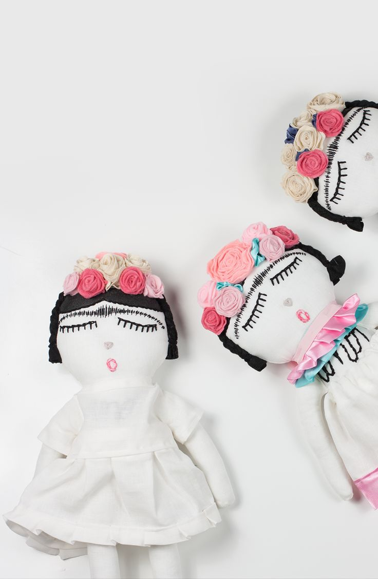 """Frida Kahlo doll, made from organic cotton linen, stuffed with hypoallergenic polyfill and is approximately 22 inches tall. Frida rocks a removable organic linen skirt, sewn-on handmade flower crown, and adorable pink shoes. """"Amor"""" is hand-stitched onto her chest. Due to the handmade nature of these dolls, no two dolls are the same."""