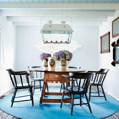 For a modern twist on Colonial classics, the designer chose a large, bright blue braided rug and seat covers based on minimalist paintings. English and early-American antiques, such as the dining table and chairs, contrast with the contemporary painted ceiling that brightens the room. (Photographer: William Abranowicz. Writer: Steele Thomas Marcoux)