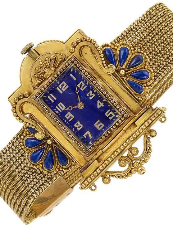 Circa 1870 Archaeological Revival Gold and Lapis Mesh Slide Bracelet Watch, centering a rectangular blue enamel dial with applied gold Arabic numerals, set within a case of architectural form, accented with gold balls, flanked by a fan of 10 pear-shaped cabochon lapis edged by small gold balls, completed by a herringbone link mesh bracelet accented by lapis slides of similar design, movement signed Koehn.