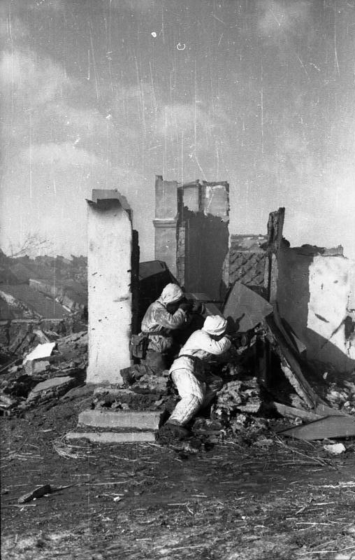 """Sowjetunion-Mitte / bei Bjelgorod.- Zwei Infanteristen der Division """"Grossdeutschland"""" in Winter-Tarnkleidung in Deckung einer Hausruine im Gefecht, bewaffnet mit sowjetischen Beute-Maschinenpistolen; 1943"""