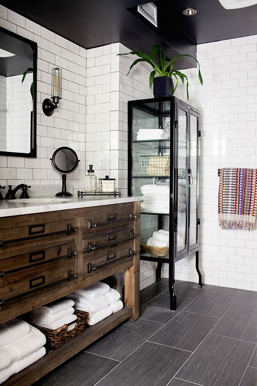 You can't go wrong with the black and white paint pairing of this industrial-inspired bathroom. But the real standout in this space is the furniture. Elegant pieces such as this glass and black lacquer display cabinet can take your bathroom from average to inspired.
