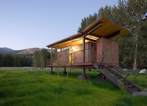 An augmented butterfly roof, natural wood, steel, and stilts finish this lovely little place of respite.