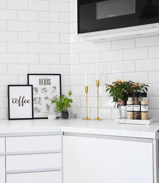 Tavlor och posters till inredning i kök. Vit inredning med guld detaljer. Vackert vitt liggande kakel.
