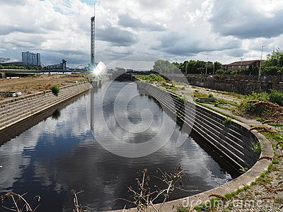 Disused dock at site of former Clydeside shipyard in Glasgow, Scotland. Reflections of clouds on water and sun on Glasgow Science Centre in distance.