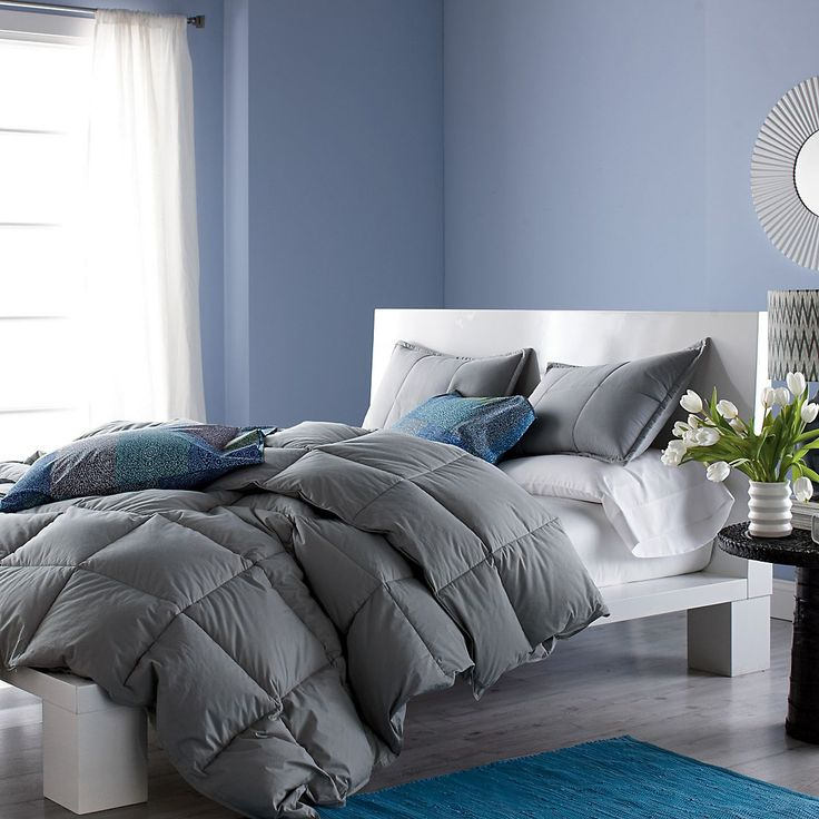 fluffy grey duvet with colorful pillows and patterned sheets