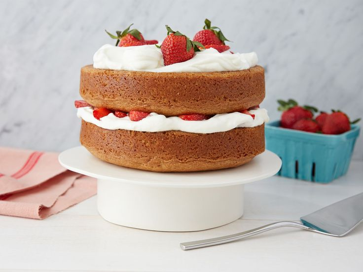 Strawberry Country Cake : Ina Garten flavors this impressive country cake with sour cream and the zest from lemon and orange. Spread generous spoonfuls of whipped cream between the cake layers and on top before adding fresh strawberries for a decorative picnic table centerpiece.