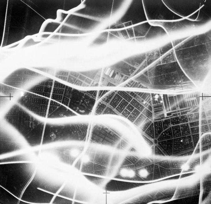 Unknown photographer, Sept. 2/3, 1941, Royal Air Force bomber command -- Vertical night aerial photograph taken during a raid on Berlin, showing bombs exploding in the vicinity of the central cattle-market and railway yard (middle right), east of the city centre. The broad wavy lines are the tracks of German searchlights and anti-aircraft fire can also be seen. Also illuminated by the flash-bomb in the lower half of the photograph are the Friedrichshain gardens and sports stadium, St. ...