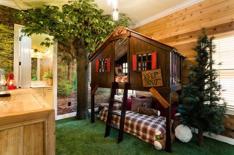 """This enchanting bedroom features a bunk bed that's constructed to resemble a tree house, complete with a """"keep out"""" sign and small ladder."""