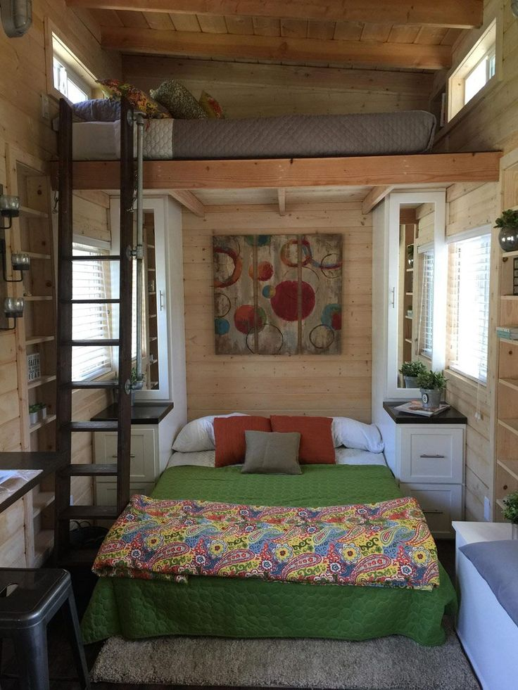 This bed folds up and turns into a couch. The bedspread and art make this little home extra cozy. | Tiny Homes
