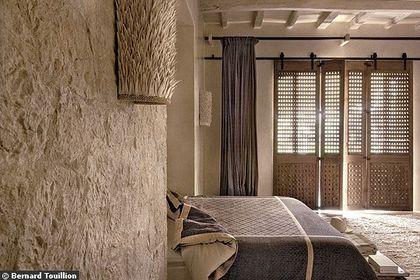 Dans une chambre dépouillée, des harmonies de lumière filtrent par les volets intérieurs en bois de cèdre
