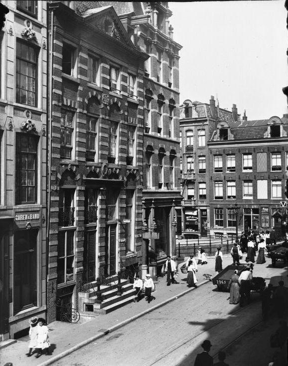 Wie de straat weet is een echte Oud Amsterdammer! Jawel: Jodenbreestraat (richting Nieuwmarkt) met zicht op Rembrandthuis-museum.  Oorspronkelijk heet de straat Sint Antoniesbreestraat, nadat vanaf 1619 zich er veel Joden vestigden werd de straat Jodenbreestraat genoemd. Tijdens de tweede wererldoorlog werden veel Joden gedeporteerd en werden de huizen geplunderd en het hout opgestookt. Hierdoor raakte de huizen in de jaren na de oorlog in verval.