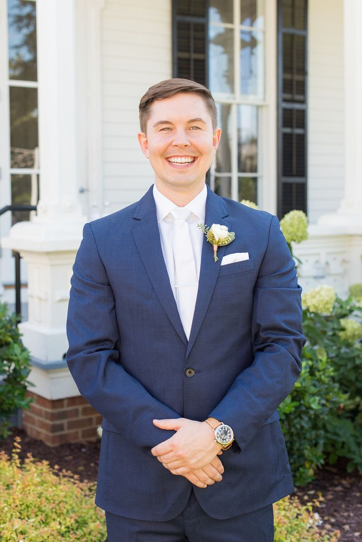 Mikkel Paige Photography pictures from a wedding at Merrimon-Wynne House in Raleigh, NC. Photo of the groom in a blue linen suit, white tie and boutonniere tied with copper wire.