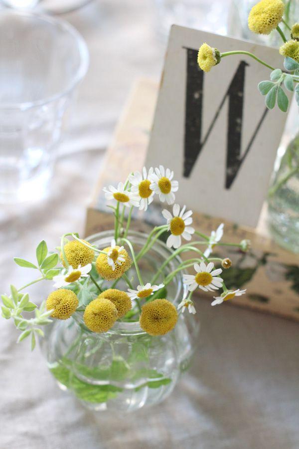 ゲストテーブル装花には2種のマトリカリアをさりげなく入れて。 洋書やアンティークなテーブル札も一緒にディスプレイ。