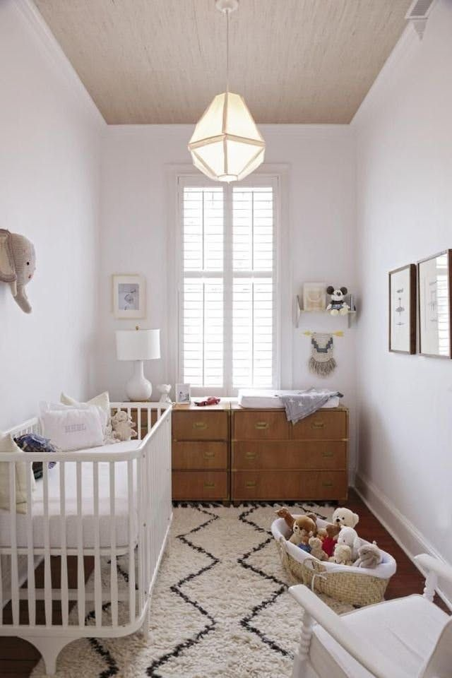 Neutral nursery design in a small baby room featuring tan grass mat wallpaper on the ceiling, white walls, two antique chests as storage, elephant head wall decor, global wall art, a small macramé wall hanging, beige and gray Moroccan rug, a basket for stuffed toys, a vintage modern style hanging pendant light, and a white rocking chair. The white and beige color palette keep this tiny gender neutral nursery from feeling too tight - Unique Nursery Ideas & Children's Room Decor - apartment…