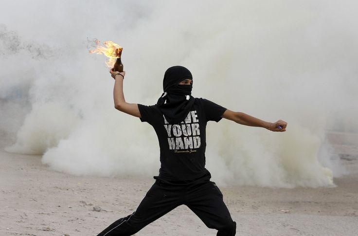 An anti-government protester throws a molotov cocktail at riot-police during clashes at the mourning procession of Ahmed Ismael Abdulsamad in the village of Salmabad south of Manama, April 2, 2012.  This reminds me of Banksy