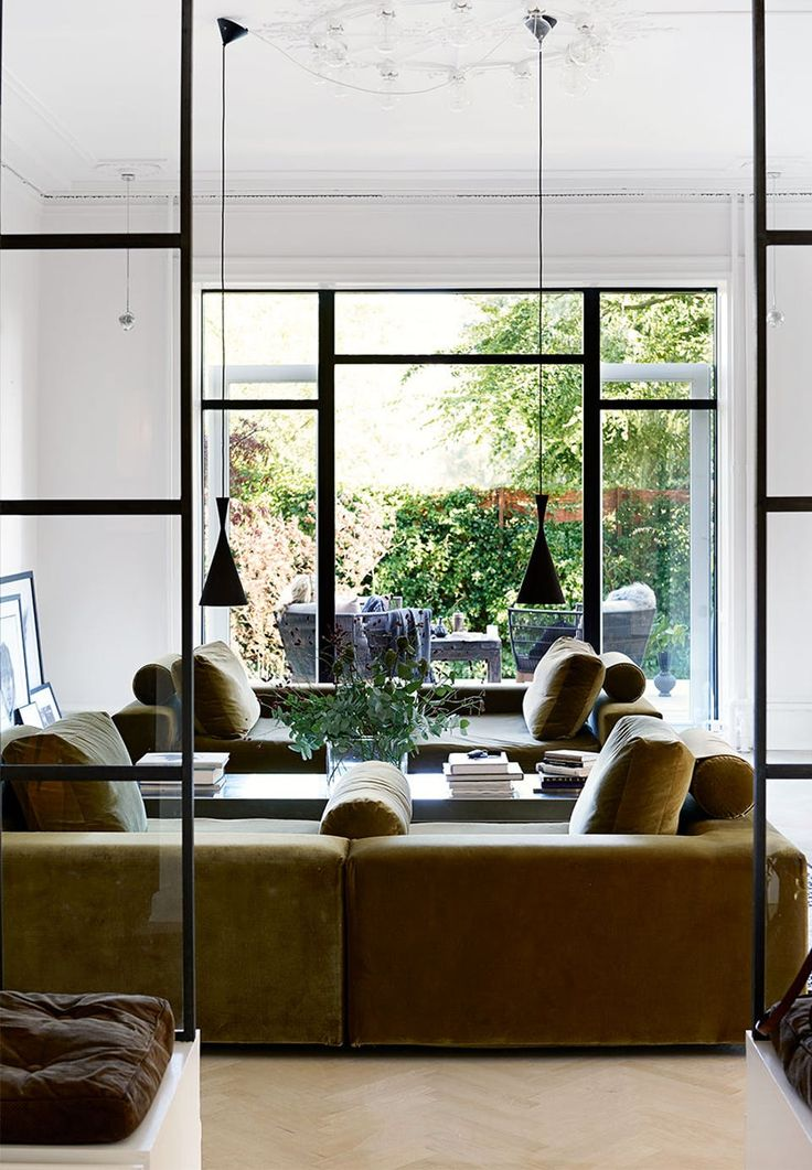 Symmetry in this lovely living room - the industrial look from the Newyorker windows in the room, is repeated in the windows to the garden. It gives a fantastic contrast to the retro-inspired green velvet sofas.